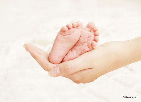 Baby Newborn Feet in Mother Hands. New Born Kid Foot, Family Love Concept