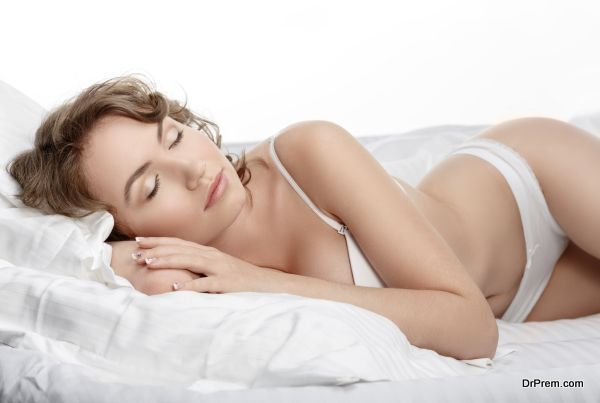 Sexy young woman is sleeping in her bed. Girl in lingerie on the bed. Sexy brunette on white bed sheets. The morning sun in the bedroom.