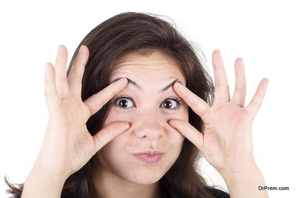 pretty young asian girl trying make her eyes more wide with her hands