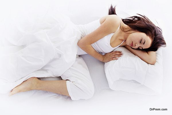Stock image of young woman sleeping on white bed