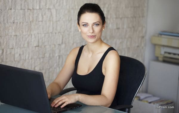 Brunette accountant typing on laptop in office, summer indoor portrait