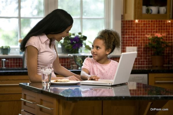 Mother and daughter in kitchen with laptop
