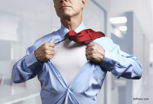 Superhero. Mature businessman tearing his shirt off over office background