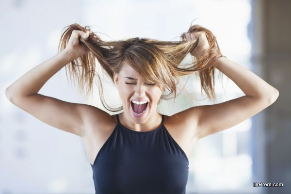 Frustrated young woman screaming and pulling her hair