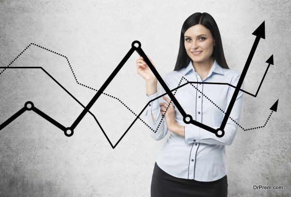 Brunette business lady presents a line graphs, which symbolise fluctuation of the business process. Concrete background.